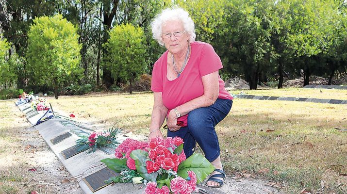 Boolarra Cemetery Trust secretary Roz Carstairs tends to a bouquet in the lawn section.
